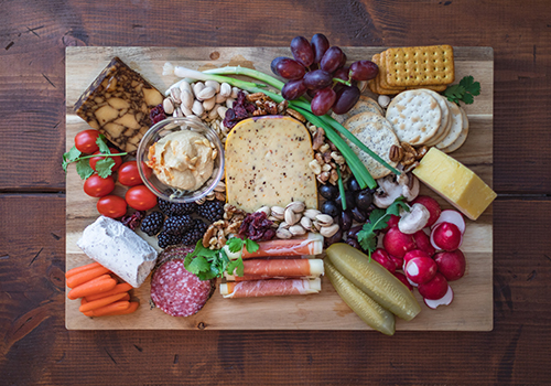 Top-down photo of a cheese board with different types of cheese, pickles, cold meat, fruit, vegetables, nuts and crackers.