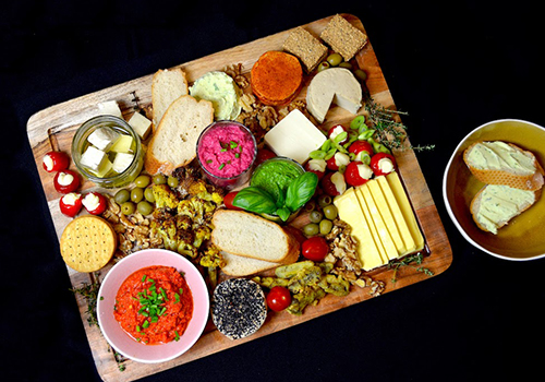 Vegan cheese board with dairy-free cheeses, breads, roasted cauliflower and dips.
